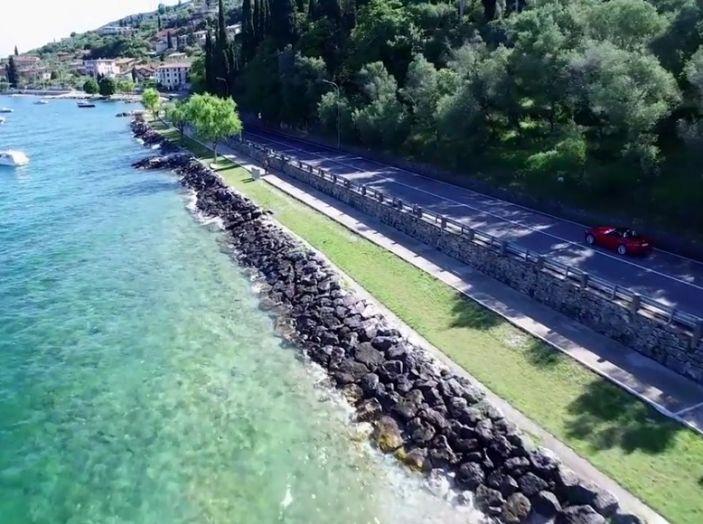 Fiat 124 Spider, vista dall'alto su strada che costeggia un lago.