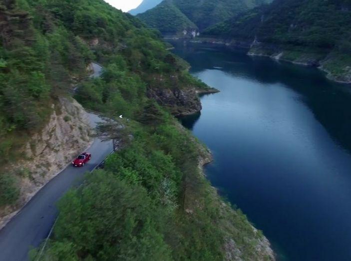 Fiat 124 Spider in movimento su strada che costeggia un lago di montagna.