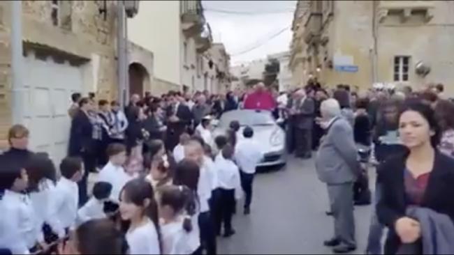 Arcivescovo saluta i fedeli da una Porsche trainata da 50 bambini
