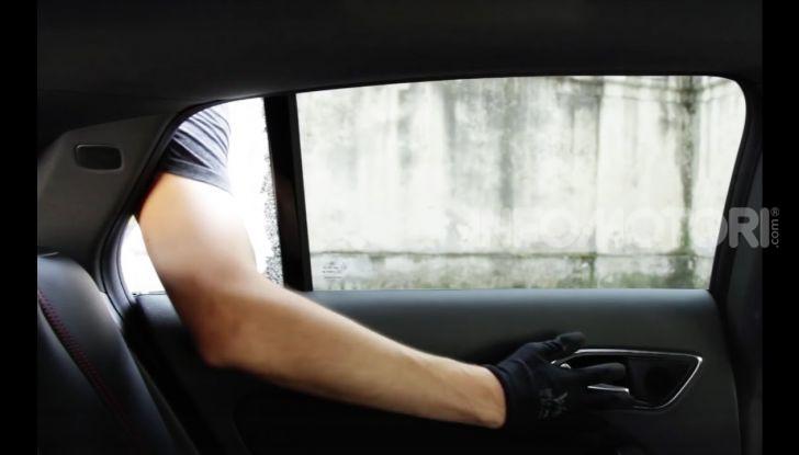 Un ladro rompe il vetro di un'automobile