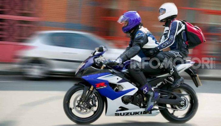 Pilota e passeggero su moto sportiva in strada