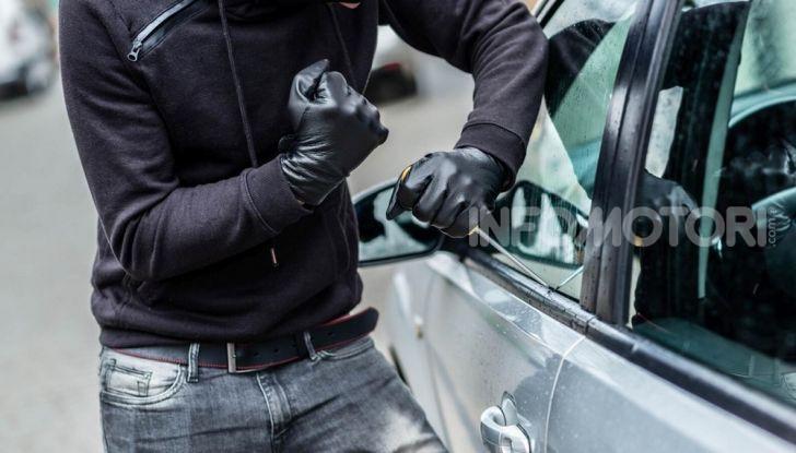 Un ladro rompe i vetri di un auto durante un furto